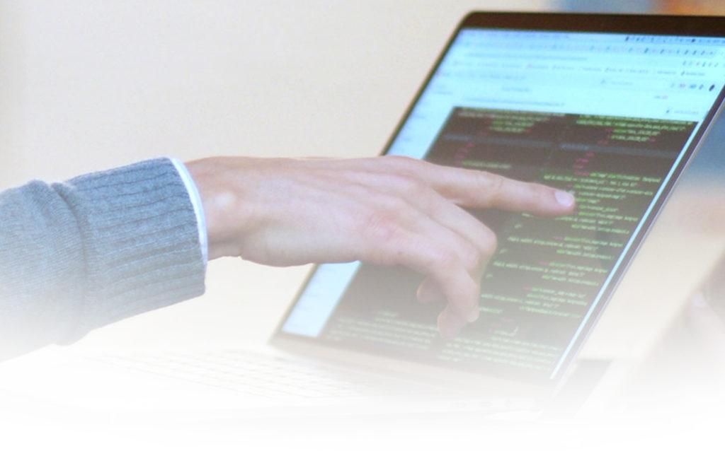 Hand zeigt auf Bildschirm mit Code
