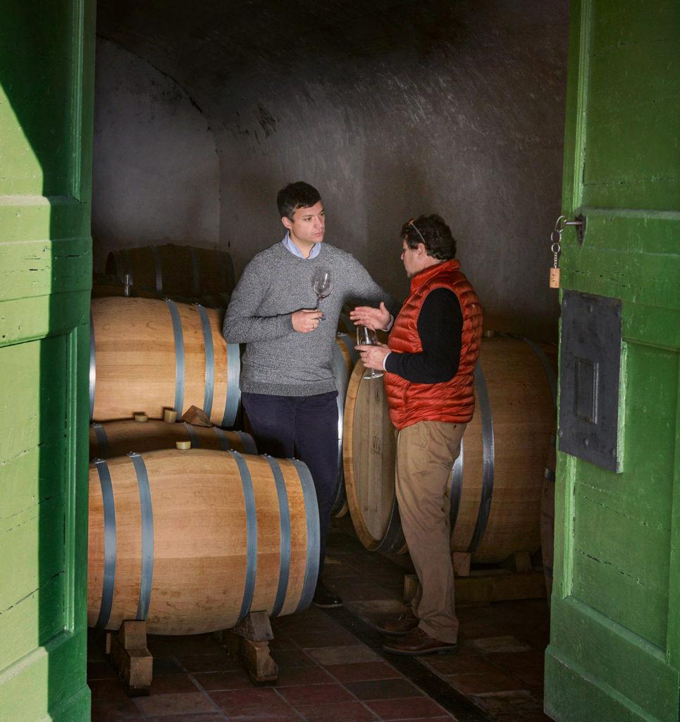 Ein Beispiel aus der Foto-Reportage: Zwei Männer stehen in einem Keller und degustieren Wein.