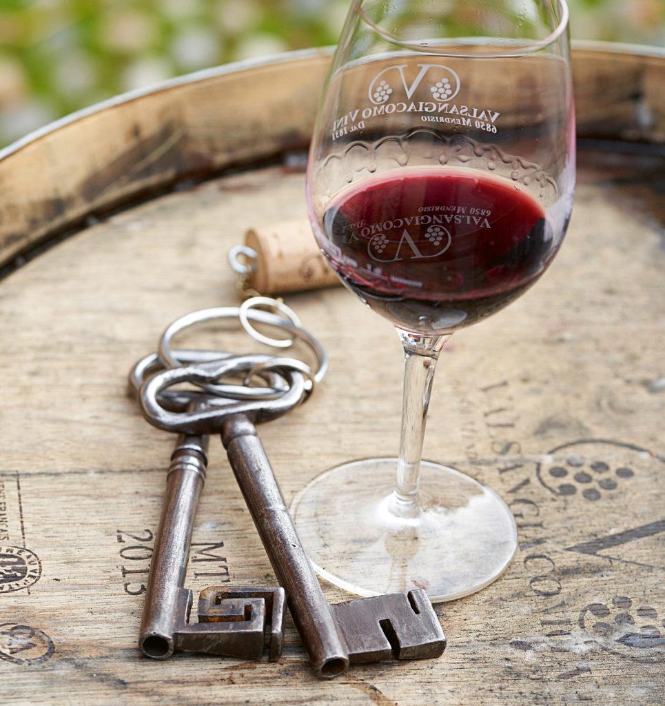 EIn Beispiel aus der Foto-Reportage: Ein Glas Wein und zwei Schlüssel liegen auf einem Holzfass