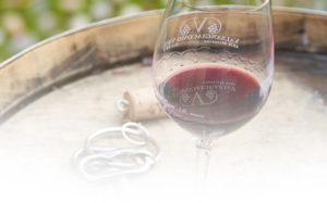 Ein Glas Wein und ein paar Schlüssel auf einem Holzfass